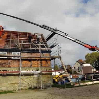 Unser Ladekran mit unserer Schuttmulde unterstützt bei Dachdeckerarbeiten
